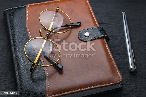 istock Glasses, notepad, pen lay on a dark table. 993114236