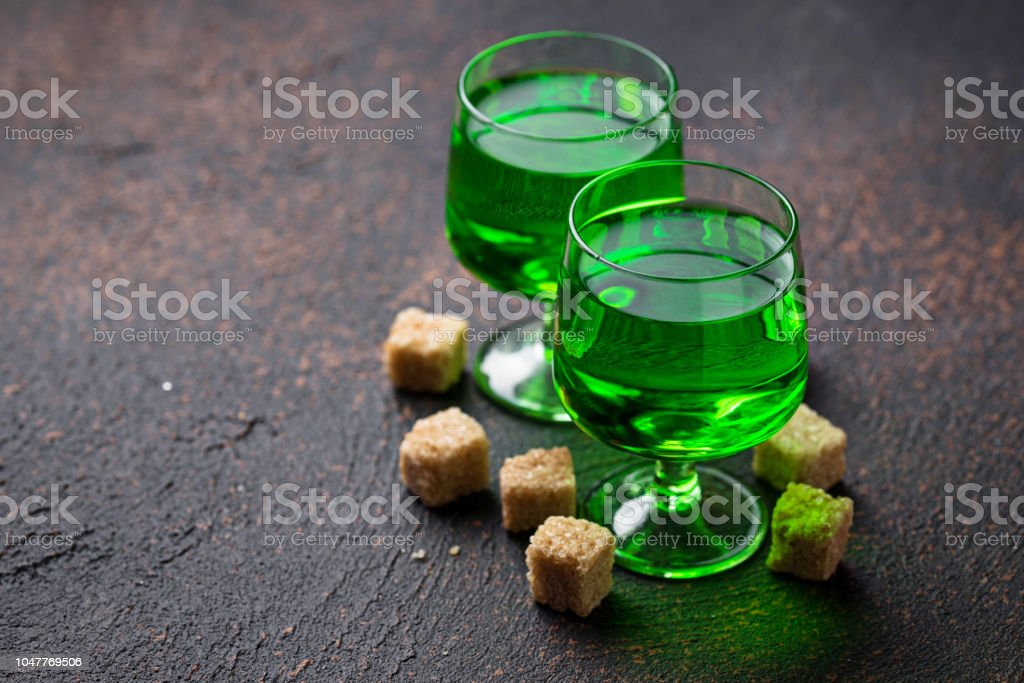 Glasses of absinthe with brown sugar stock photo