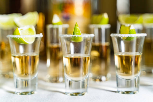 Glasses of alcohol and lime on the restaurant table. Glasses of alcohol and lime on the restaurant table. Selective focus and copy space, tequila shots, vodka,whisky, rum with lemon. tequila shot stock pictures, royalty-free photos & images