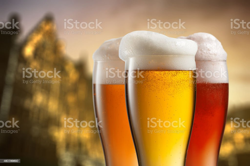 Glasses of beer against blurred european city stock photo
