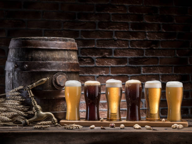 Glasses of beer and ale barrel on the wooden table. Craft brewery. stock photo