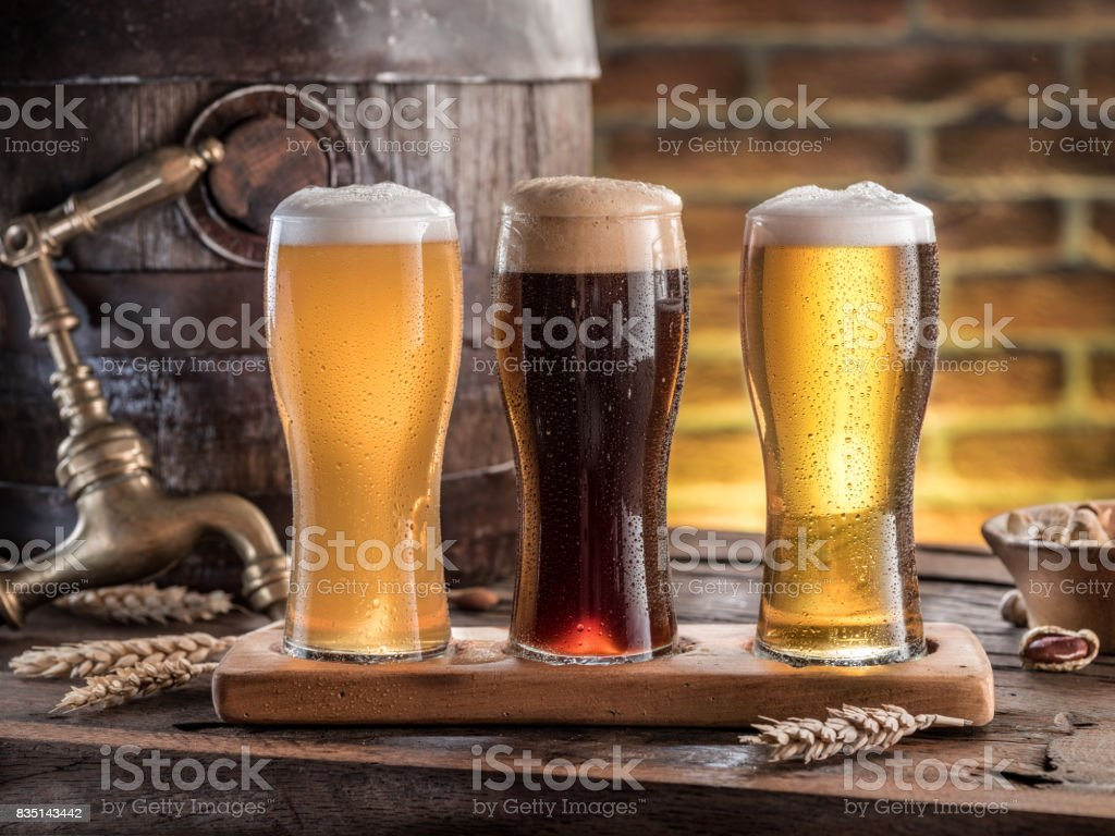 Glasses of beer and ale barrel on the wooden table. Craft brewery. – zdjęcie