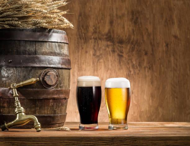 copos de cerveja e cerveja de barril na mesa de madeira. cervejaria artesanal. - ale - fotografias e filmes do acervo