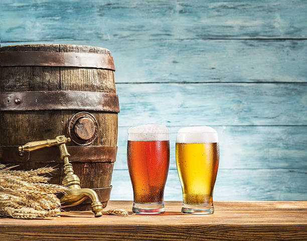 Glasses of  beer and ale barrel on the wooden table. - foto stock