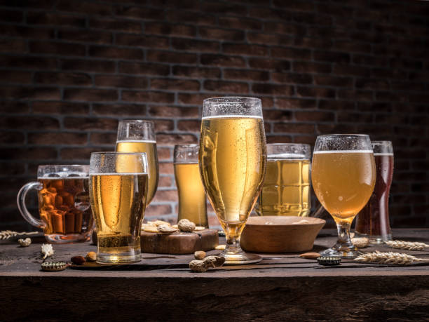 Glasses of beer and snacks on the wooden table. Glasses of beer and snacks on the wooden table. lager stock pictures, royalty-free photos & images
