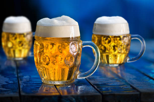 Glasses of beer on the blue wooden background. stock photo
