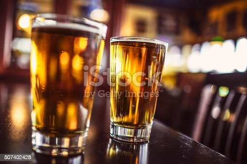Two glasses of beer on a bar counter.