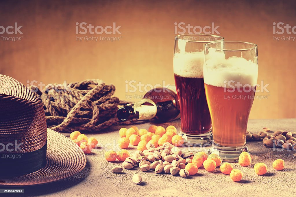 Glasses of beer, rope, cheese balls, bottle and pistachio nuts royalty-free stock photo