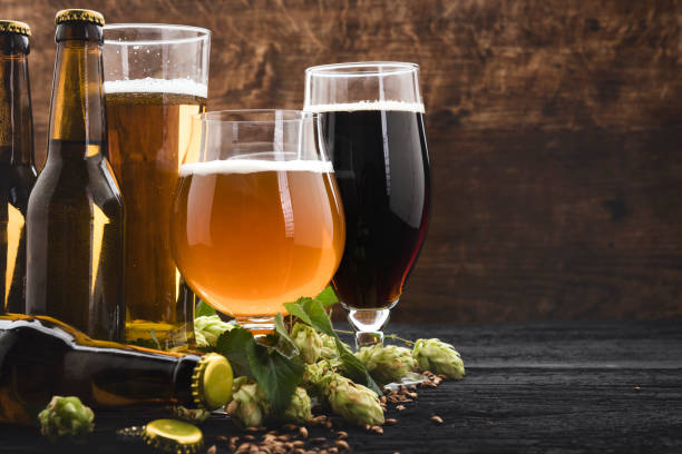 Glasses of beer with green hops and wheat beer and ingredients beer alcohol stock pictures, royalty-free photos & images