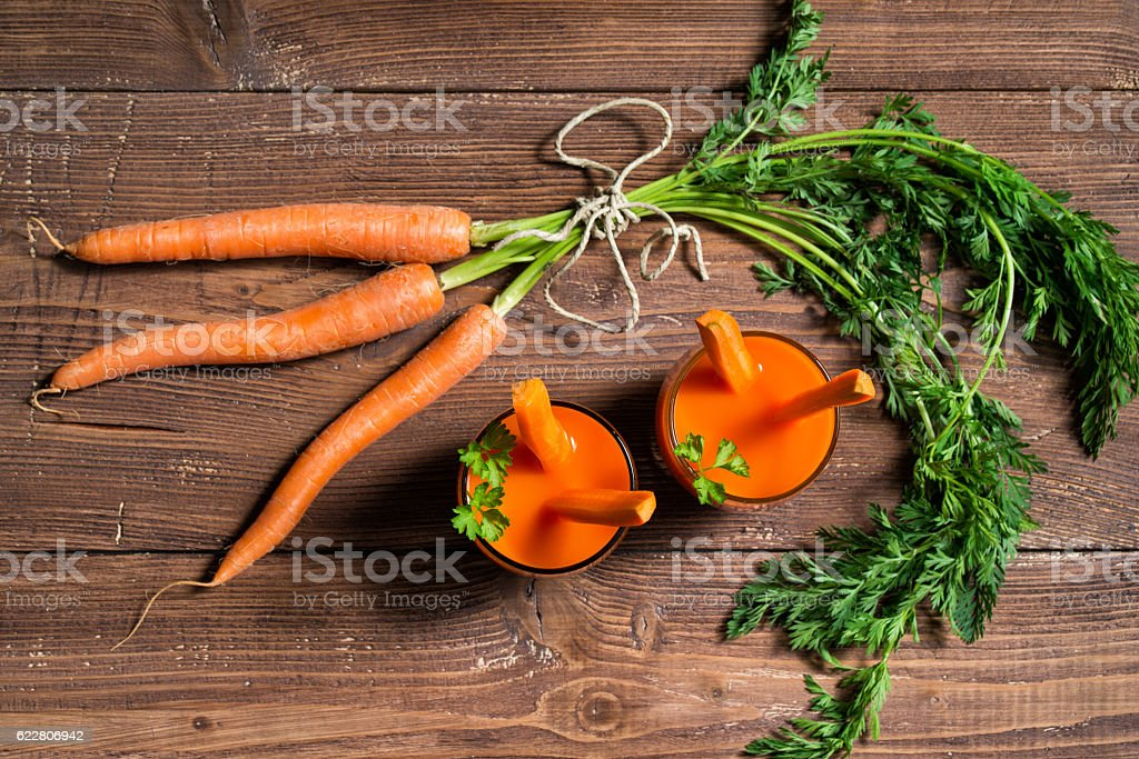 Glasses of carrot juice and fresh carrots stock photo