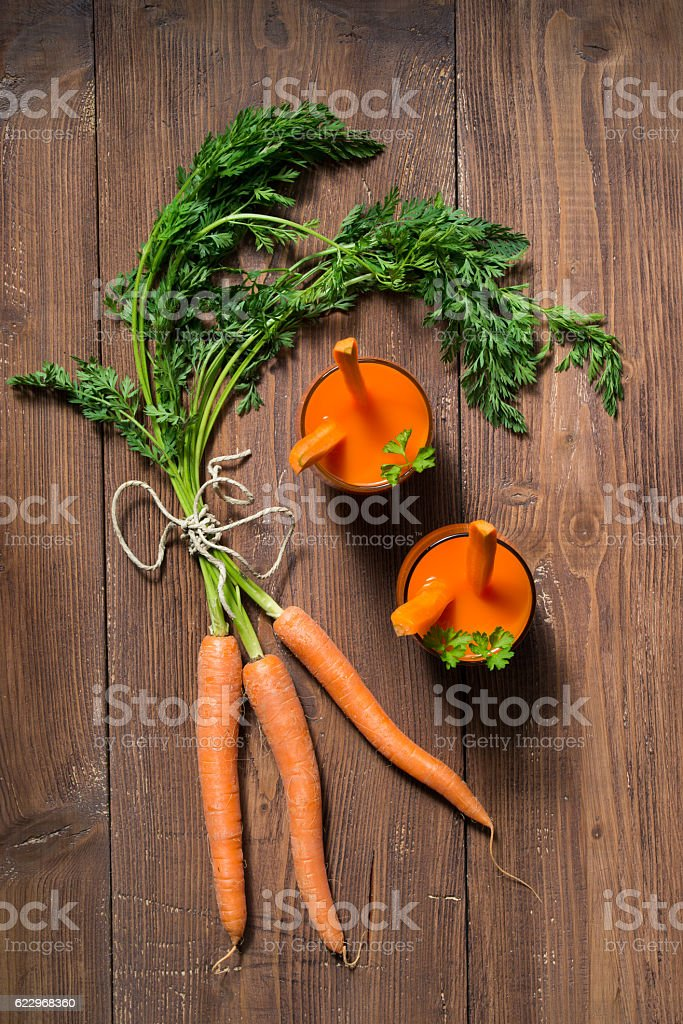 Glasses of carrot juice and fresh carrots, wooden background stock photo
