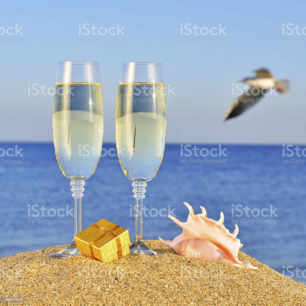 Glasses of champagne, box with a gift  and seashel royalty-free stock photo
