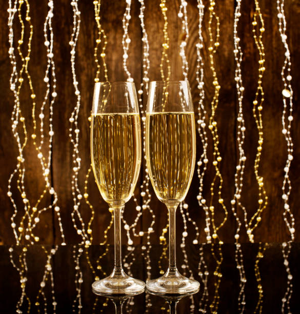 Glasses of champagne on a wooden background with shiny background and reflections. Celebration concept with free space for text. White wine. Glasses of champagne on a wooden background with shiny background and reflections. Celebration concept with free space for text. White wine. sopaatervinning stock pictures, royalty-free photos & images