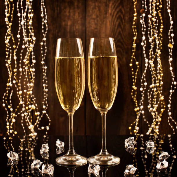 Glasses of champagne on a wooden background with shiny crystals and garlands. Celebration concept with free space for text. Happy New Year! Glasses of champagne on a wooden background with shiny crystals and garlands. Celebration concept with free space for text. Happy New Year! sopaatervinning stock pictures, royalty-free photos & images