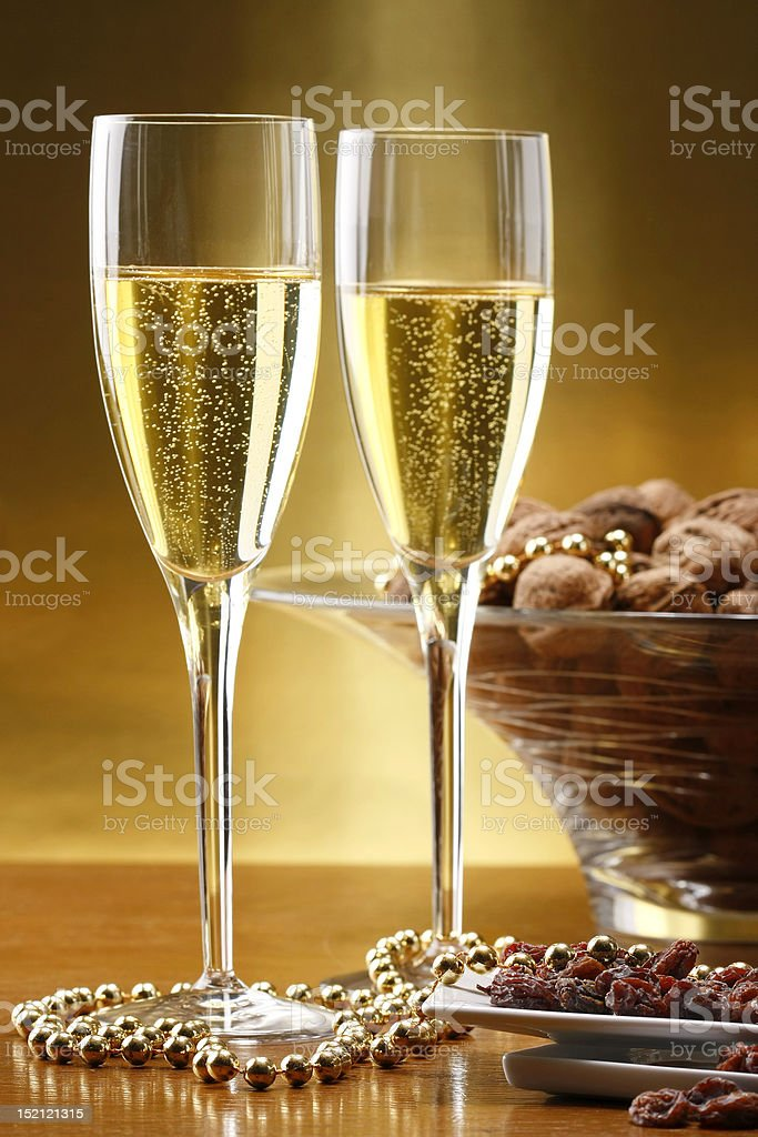 Glasses of champagne with gold background with walnuts dryed raisins