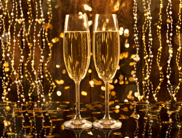 Glasses of champagne with bubbles on a wooden background with shiny gold confetti. Celebration concept. New Year background. White wine. Glasses of champagne with bubbles on a wooden background with shiny gold confetti. Celebration concept. New Year background. White wine. sopaatervinning stock pictures, royalty-free photos & images
