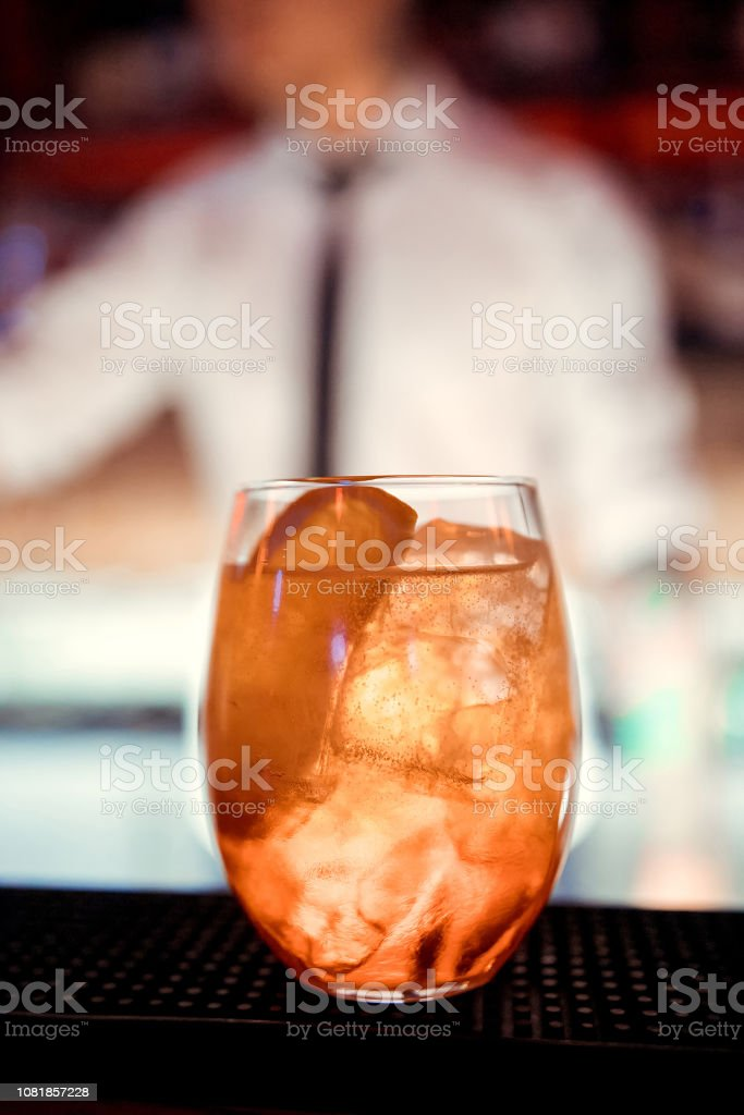 glasses of cocktails on the bar. bartender pours a glass of sparkling wine with Aperol. stock photo