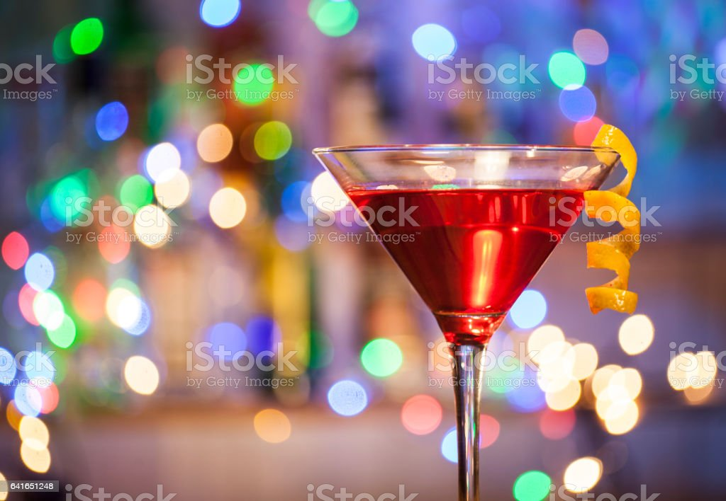 Glasses of cosmopolitan cocktail on a bar lights background. stock photo