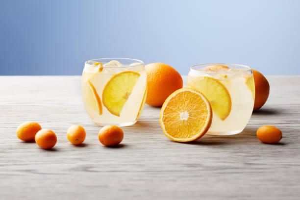 leckere limonade mit reifer orangen auf hölzernen tischplatte gläser - innocent saft stock-fotos und bilder