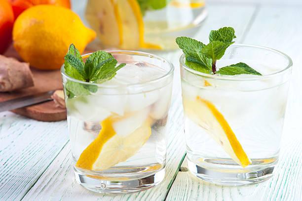 glasses of detox drink with lemon and mint - ingwerwasser zubereiten stock-fotos und bilder