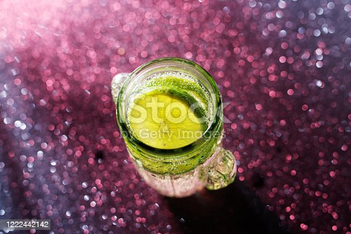 1129427811 istock photo Glasses of drinks on sparkling background. Holiday party, celebration concept. Free space for text. Iridescent glare on the glass. Coctail or soda drink with slice of lime. Top view. 1222442142