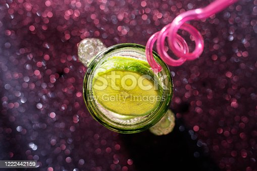 1129427811 istock photo Glasses of drinks on sparkling background. Holiday party, celebration concept. Free space for text. Iridescent glare on the glass. Coctail or soda drink with slice of lime. Top view. 1222442159
