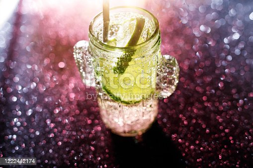 1129427811 istock photo Glasses of drinks on sparkling background. Holiday party, celebration concept. Free space for text. Iridescent glare on the glass. Coctail or soda drink with slice of lime. Top view. 1222442174