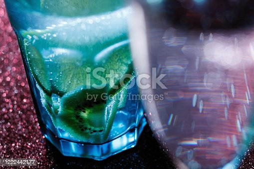 1129427811 istock photo Glasses of drinks on sparkling background. Holiday party, celebration concept. Free space for text. Iridescent glare on the glass. Coctail or soda drink with lime. 1222442177