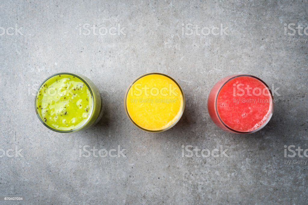 Glasses of fresh juice on gray stone table stock photo