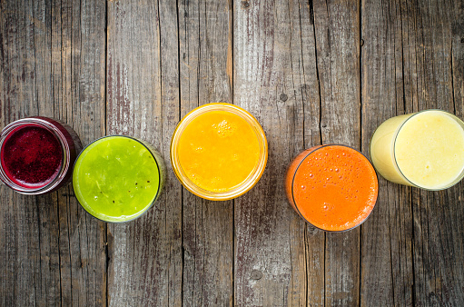 Glasses of fresh juice on an old wooden table
