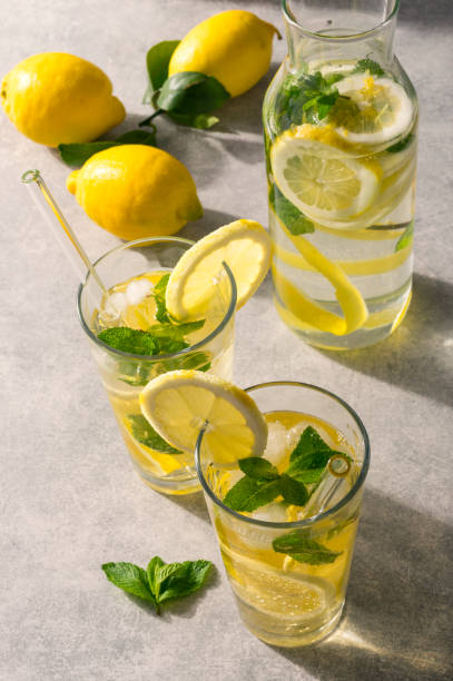 Glasses of homemade lemonade with ice and fresh mint on sunny table. Concept for healthy detox drink with eco-friendly glass straw. stock photo