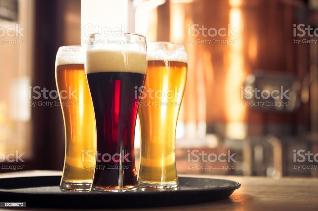 Glasses of lager and ale beer in front of copper vat Glasses of lager and ale beer on the table in the microbrewery. Copper vat in the background. No people. After Work Stock Photo