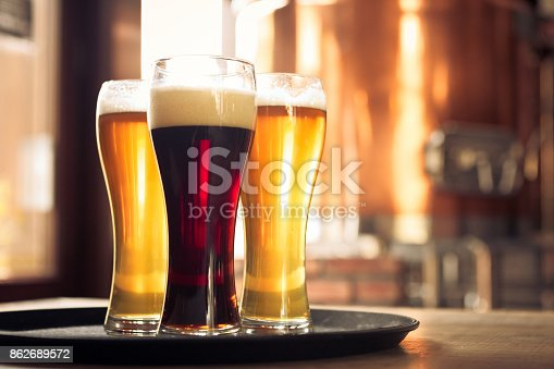 istock Glasses of lager and ale beer in front of copper vat 862689572