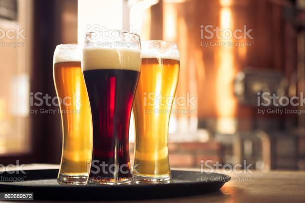 Glasses Of Lager And Ale Beer In Front Of Copper Vat Stock Photo - Download Image Now