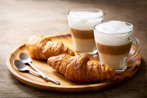 glasses of latte macchiato coffee and croissants stock photo