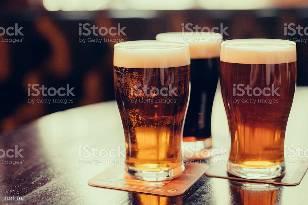 Glasses of light and dark beer on a pub background. stock photo
