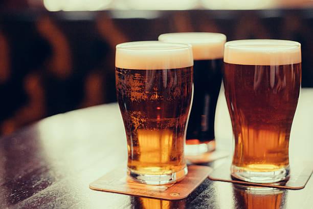グラスの明るい色と濃色のビールパブを背景にしています。 - ビール ストックフォトと画像