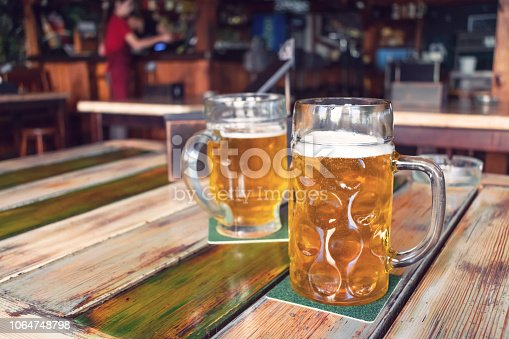 istock Glasses of light beer on pub background. Pint glass of golden beer with snacks and grill food on wooden table in pub, bar 1064748798