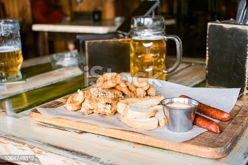 istock Glasses of light beer on pub background. Pint glass of golden beer with snacks and grill food on wooden table in pub, bar 1064748812