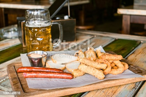 istock Glasses of light beer on pub background. Pint glass of golden beer with snacks and grill food on wooden table in pub, bar 1064748816
