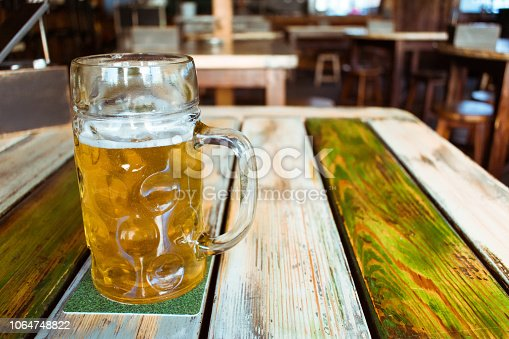 istock Glasses of light beer on pub background. Pint glass of golden beer with snacks and grill food on wooden table in pub, bar 1064748822