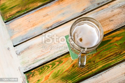 istock Glasses of light beer on pub background. Pint glass of golden beer with snacks and grill food on wooden table in pub, bar 1064748846