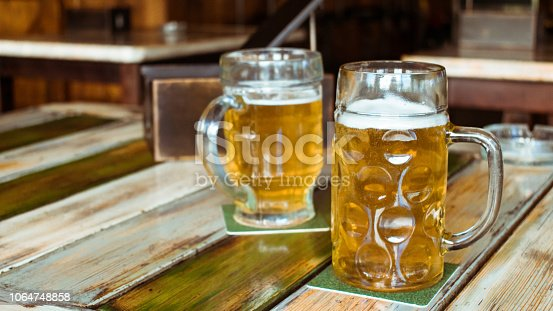 istock Glasses of light beer on pub background. Pint glass of golden beer with snacks and grill food on wooden table in pub, bar 1064748858