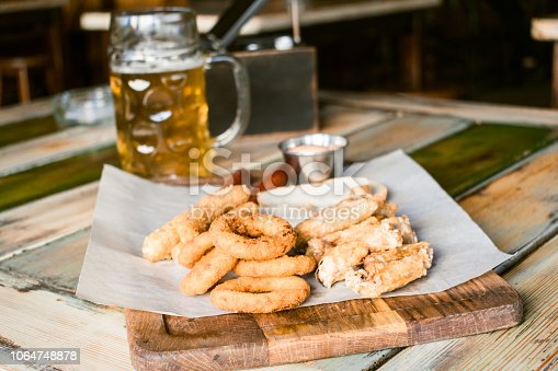 istock Glasses of light beer on pub background. Pint glass of golden beer with snacks and grill food on wooden table in pub, bar 1064748878