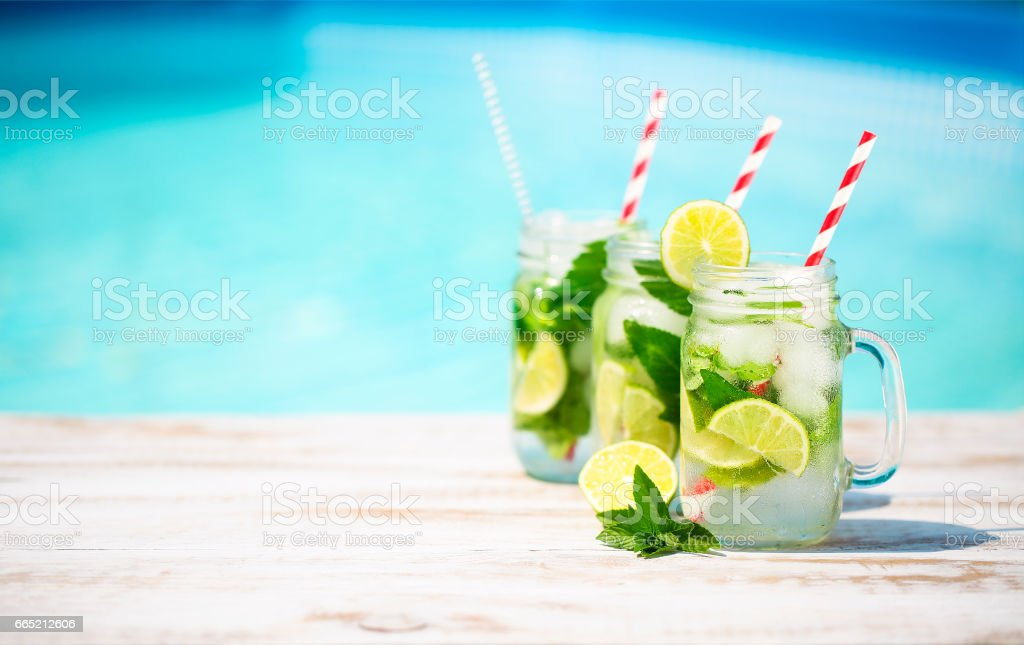 Glasses of lime lemonade near pool stock photo