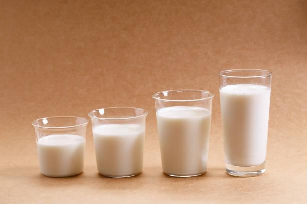 Gläser Milch als steigende Höhe angeordnet. – Foto
