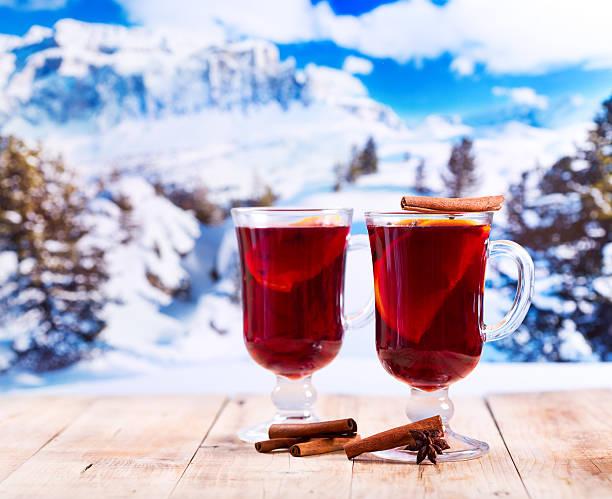 glasses of mulled wine over winter landscape glasses of mulled wine on wooden table over winter landscape apres ski stock pictures, royalty-free photos & images