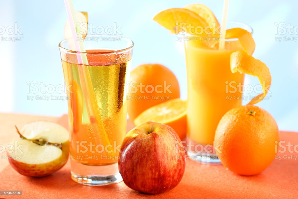 Glasses of orange and apple juice with whole frites royalty-free stock photo