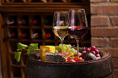 Glasses of red and white wine in wine cellar accompanied by  grapes, cheese, prosciutto, figs and nuts on wine barrel