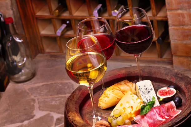 Gafas de rojo, rosa y vino blanco con uva, higos y nueces en bodega. Concepto de alimentos y bebidas - foto de stock